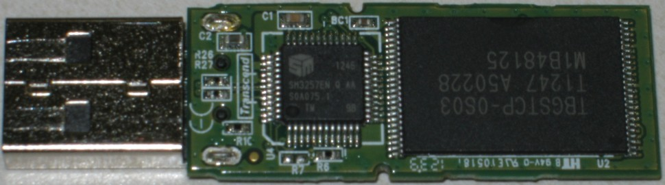 The internals of a traditional USB thumb drive. The large chip on the right is standard NAND flash memory, which can be removed and read with a device programmer.