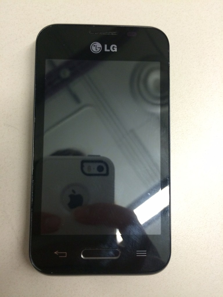 The test phone we bought, along with a reflection of my iPhone taking the picture.