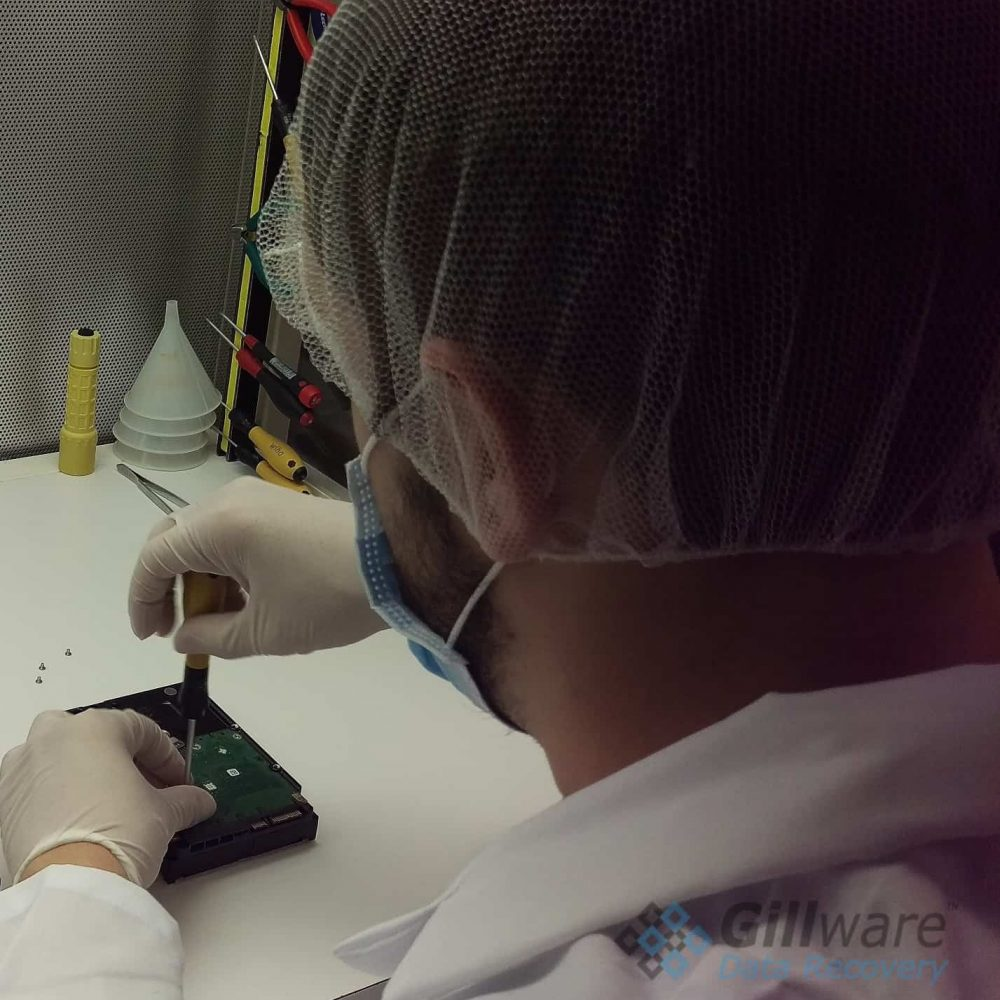 One of our RAID-0 recovery cleanroom engineers disassembling a hard drive for inspection.