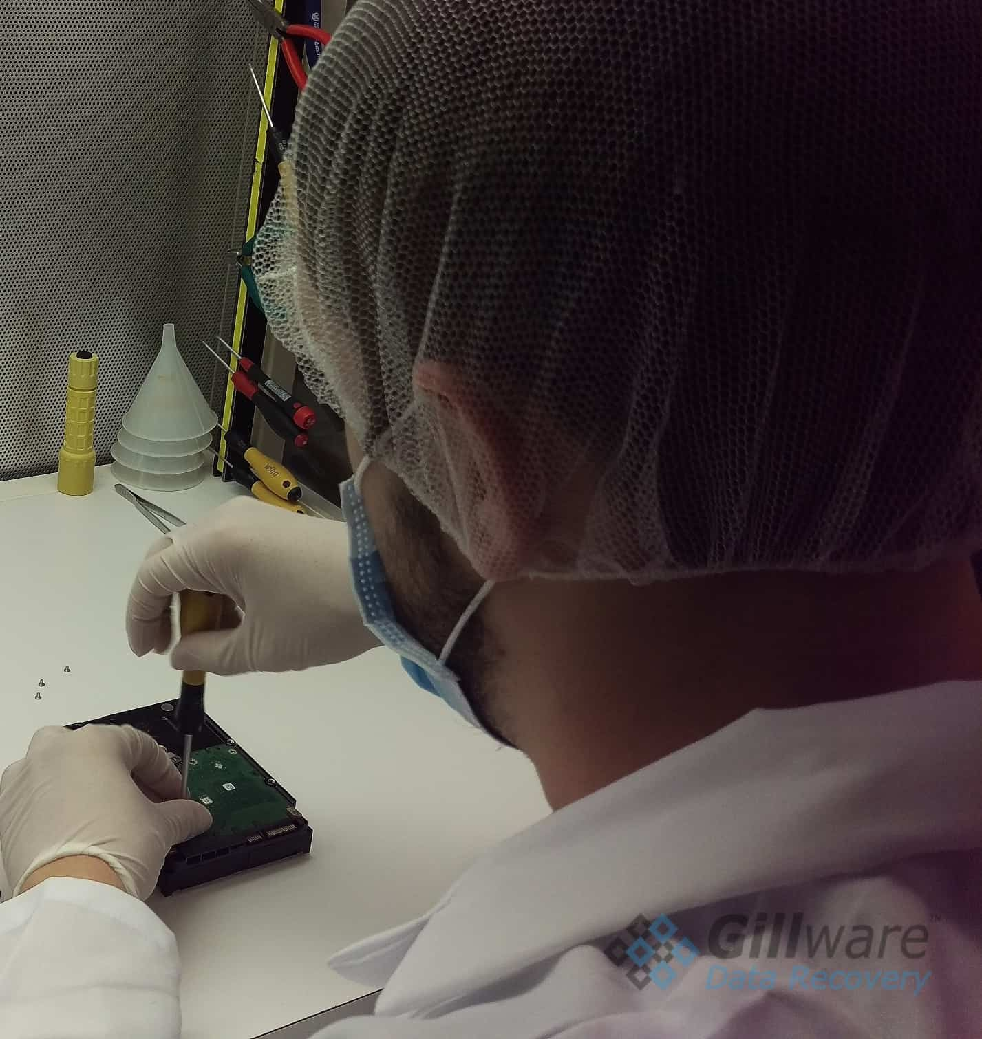 One of our RAID-0 recovery cleanroom engineers disassembling a hard drive for inspection