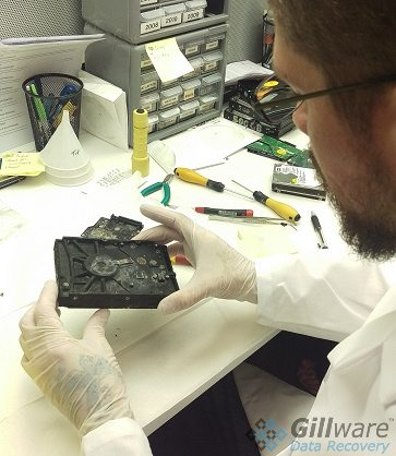 A hard drive repair engineer in one of our cleanroom benches inspects a badly burned hard drive.