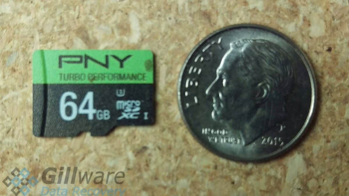 A size comparison of a 64 GB microSD card to a dime