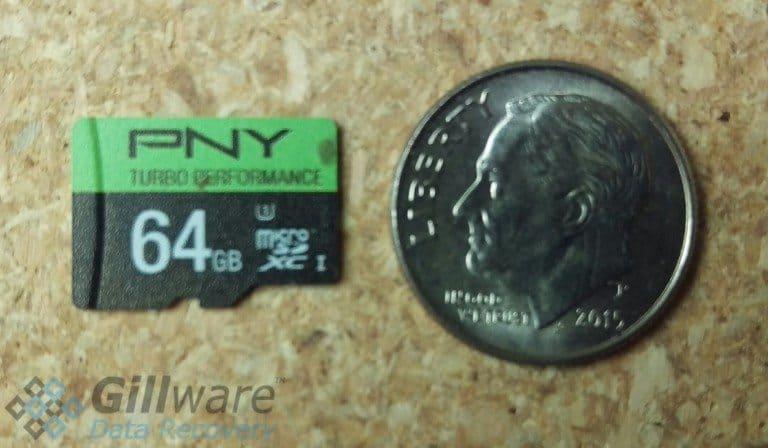 A size comparison of a 64 GB microSD card to a dime