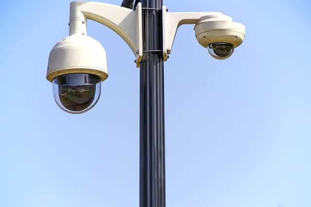 Surveillance cameras on a post with blue sky in the background