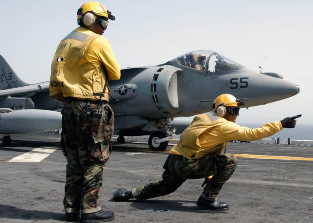 Two Navy men on Air Craft Carrier directing jet for take off.
